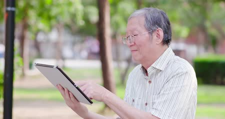 в отставке : Older man use tablet in the park Стоковые видеозаписи