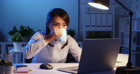ноутбук : asian woman overtime work and drink tea or coffee in the office