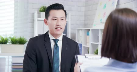 internar : confident asian man talk to female interviewer for a job interview
