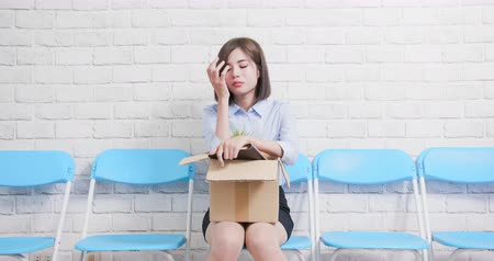 licenziamento : Asian businesswoman is fired with box hoding in hand and feel down