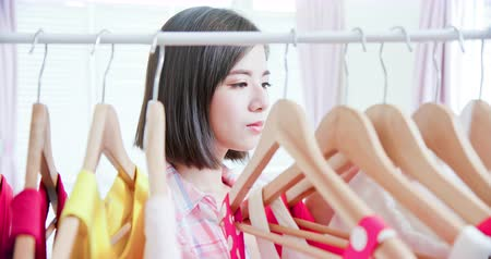 решить : young woman choosing clothes on a rack at home Стоковые видеозаписи