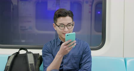 taipei : Young man take train or MRT and use the phone