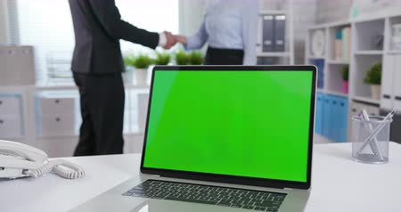 blank : laptop with green screen and business people handshake in background