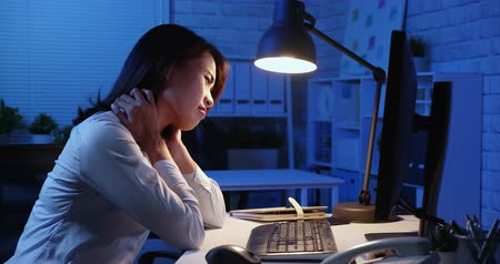 boyun : asian woman overtime work along and feel tired in the office Stok Video