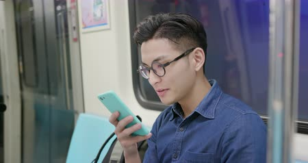public transportation : young man take train or MRT and use the phone