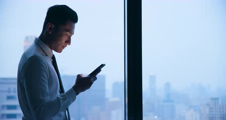послать : Asian businessman use cellphone at night in the office