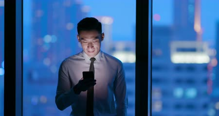 the city : Asian businessman use smart phone at night in the office