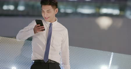 подключение : businessman use phone outdoor in the evening Стоковые видеозаписи