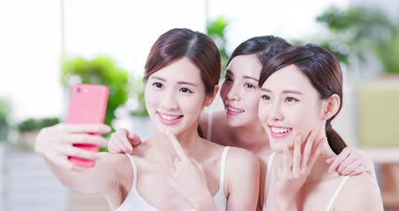 bestie : Smiling asian womans take selfie after the skin care in the spa salon