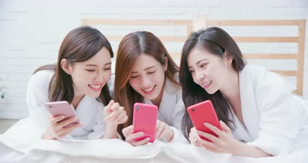 bestie : Smiling asian women wearing bathrobe are share something with the smart phone