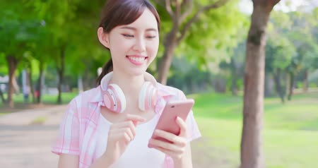 odeslat : slow motion of young asian woman use the phone with earphones while walking Dostupné videozáznamy