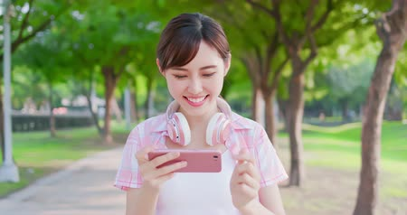 go to school : young asian girl play mobile game on her smart phone while walking