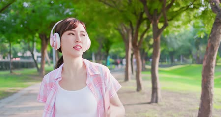 on the go : young asian woman listen to music with earphone and her smart phone while walking