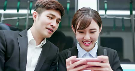 public worker : asian woman play game by smart phone with her coworker on the mrt Stock Footage