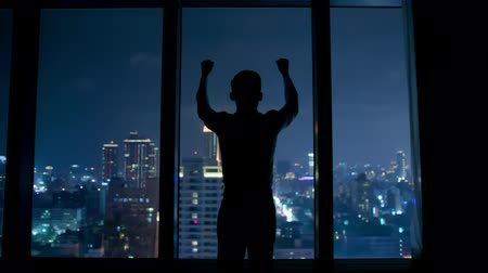 biznesmen : silhouette of success businessman standing by the window at night Wideo