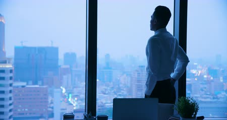 work hard : Businessman look through window when work in the night Stock Footage
