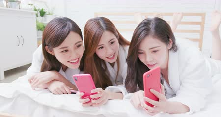 group people : Smiling asian women wearing bathrobe are share something with the smart phone