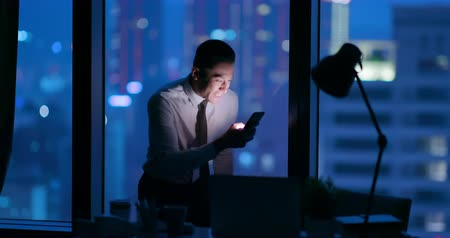 feliz : businessman work overtime with excitment and use smart phone in the office Stock Footage