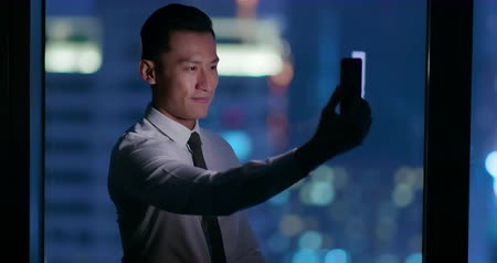 face id : businessman use facial recognition system by smartphone at night in the office