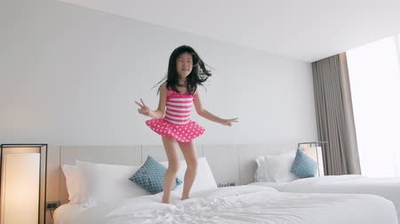 postel : slow motion of asian girl having fun jumping on bed in hotel