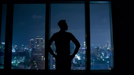 infastidito : silhouette of upset businessman watching through the window at night Filmati Stock