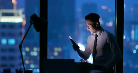 homem de negócios : businessman work excitedly at night after reading the message by smartphone