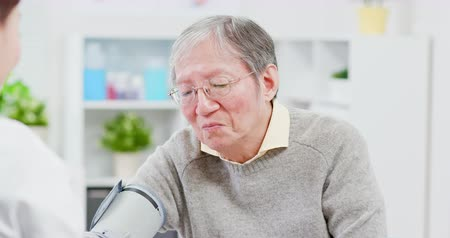 メディケア : Female doctor measure blood pressure for an elderly patient 動画素材