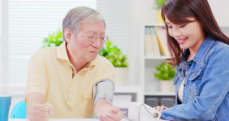 take blood : Daughter measure blood pressure for father tenderly