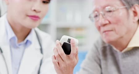 glukometr : Female doctor show blood sugar test result to elder patient and feel fine
