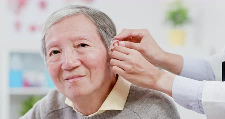 aids : Doctor help elder patient wear audiphone to improve his hearing Stock Footage