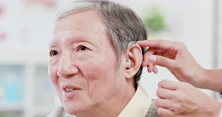 sida : Doctor help elder patient wear audiphone to improve his hearing Vídeos