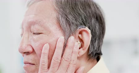 rögzített : elder patient wear audiphone to improve his hearing