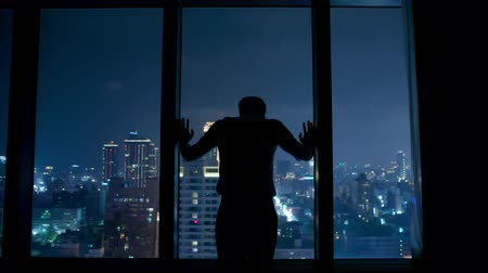 iluminado para trás : silhouette of upset businessman standing by the window at night