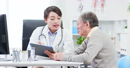 discutir : Female doctor see elder patient and discuss with him patiently