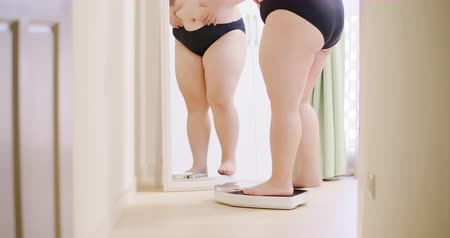 female measurements : slow motion of plus size asian girl look mirror and measure her weight by scale Stock Footage