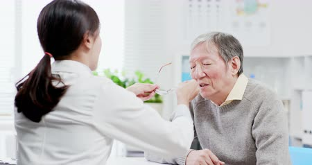 объяснение : Female ophthalmologist see an elderly patient and helping him to wear glasses