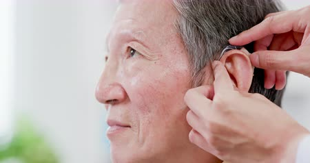 rögzített : Doctor help elder patient wear audiphone to improve his hearing Stock mozgókép