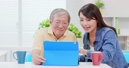 use laptop : Young daughter teach elder father use tablet pc at home Stock Footage