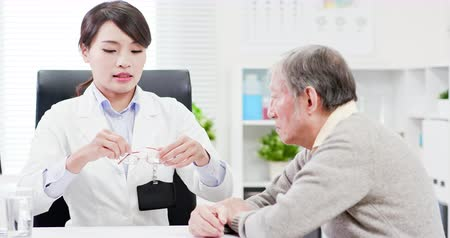 elderly care : Female ophthalmologist see an elderly patient and helping him to wear glasses