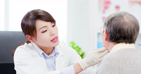 examinar : Female doctor check throat for elder patient carefully Stock Footage
