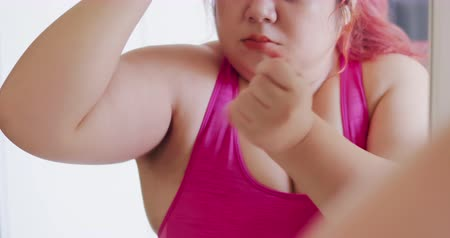 csip : Slow motion of plus size asian woman look mirrior and pinch her flabby arms