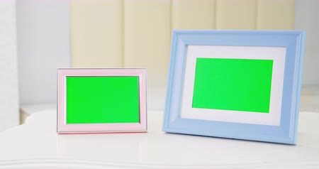 apartament : close up of blue and pink photo frame with green copy space on table at home