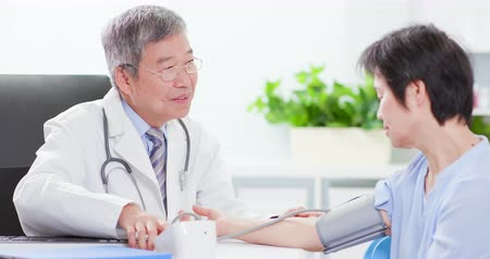 female measurements : Senior doctor measure blood pressure for asian woman carefully