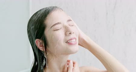 по уходу за кожей : slow motion of beauty asian woman wash her face and hair