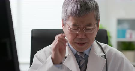 discomfort : Senior asia doctor feel tired and has headache Stock Footage