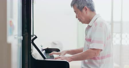 pomačkání : asian old man practice playing the piano at home