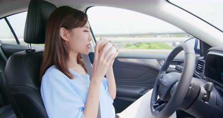 yönlendirmek : Asian woman in an autonomous self driving car and drink a coffee on the highway Stok Video