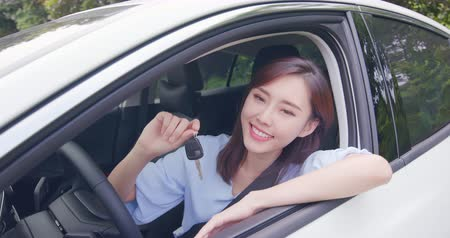 car rental : pretty woman sit in the car with key and smile happy