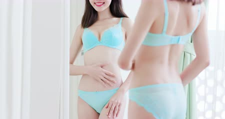 медицинская помощь : asian beauty with underwear look in mirror and is pleased about her flat belly Стоковые видеозаписи