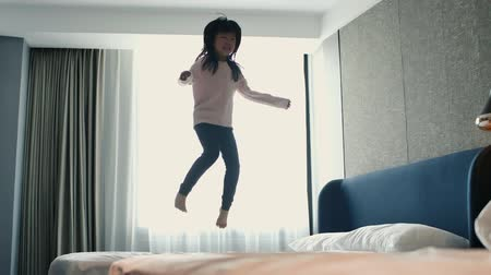giovane donna : slow motion of asian girl having fun jumping on bed in hotel